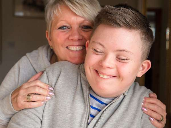 adoptive mother hugs her smiling son who has special needs