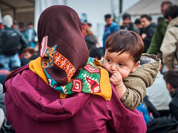 Latin American woman holds her young son as they walk through a refugee camp