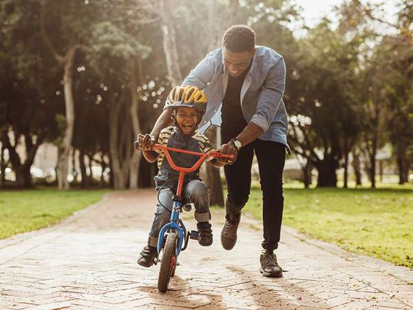 adoptive dad helps his son learn to ride a bike