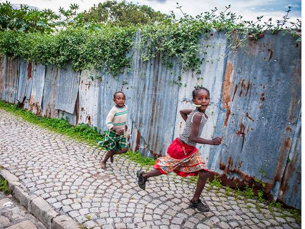 ethiopian children run on the sidewalk in ethiopia