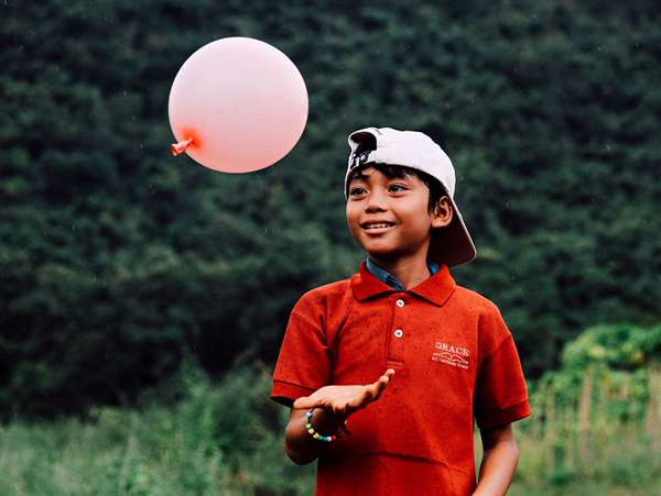 young adopted boy plays with a balloon in his backyard