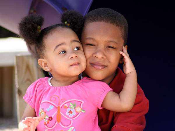 an african american teenage boy hugs his toddler sister in their foster parents' home