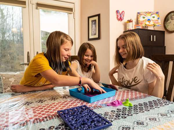 three girls in foster care play games at the kitchen table
