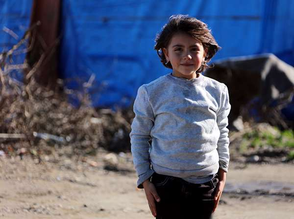 A young girl poses in front of a blue refugee tent.