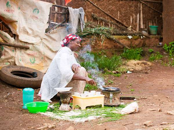 Ethiopian woman cooks rice outside her home