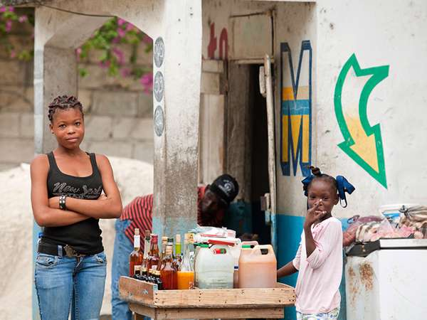 A Haitian mother sells drinks at her market stand with her young daughter