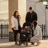 Young white adoptive couple meets with birth mother and baby on urban street