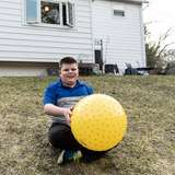 young boy in foster care plays with a large, yellow ball in the backyard