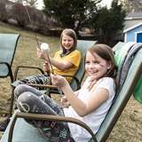 two girls roast marshmallows over a fire in the backyard of their adoptive parents' house