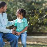 african american adoptive father speaks to his son on a park bench