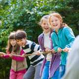 Diverse kids play tug-of-war outside