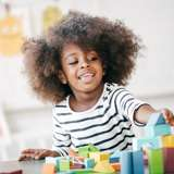 young african american girl plays with blocks