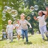diverse group of children blow bubbles in the yard